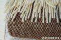 Detail hnedej vlnenej deky s bielymi strapcami