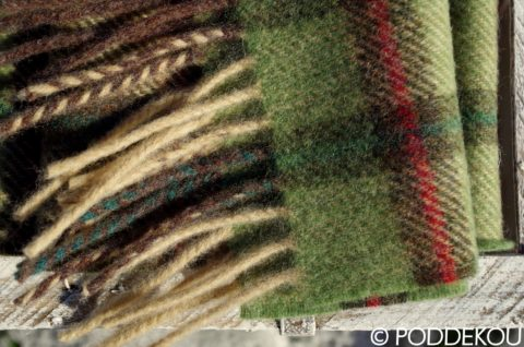 Detail hnedo-zeleného vlneného šálu so strapcami