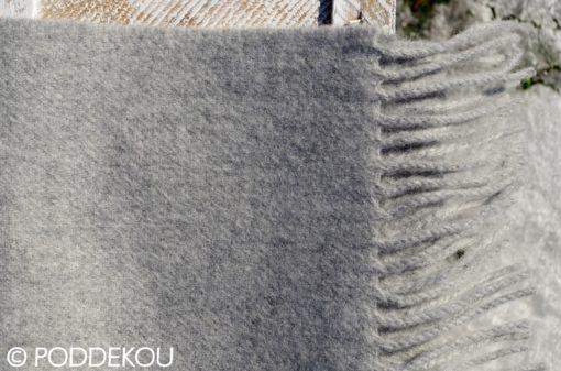 Detail vlneného svetlosivého šálu so strapcami