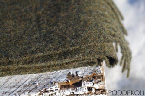 Detail vlneného olivovo zeleného šálu so strapcami