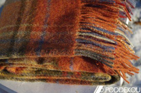 Klbko vlnenej deky s károvaným vzorom oranžovo tehlovej.