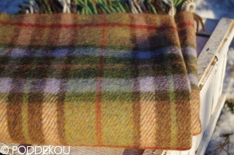 Detail tartanovej vlnenej deky zeleno-hnedej