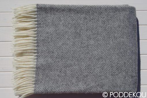 Sivo-biela vlnená deka so vzorom rybia kosť so strapcami.