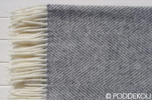 Detail vlnenej deky sivo-bielej so vzorom rybia kosť a strapcami.