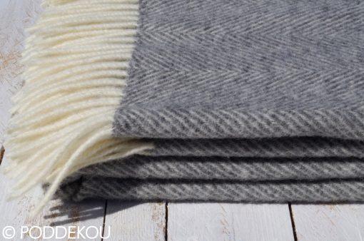 Detail sivo-bielej deky so vzorom rybia kosť so strapcami