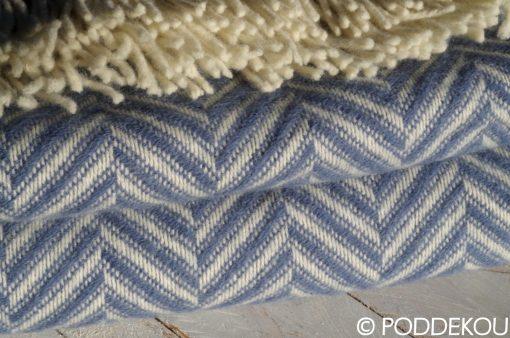Detail modro-bielej deky herringbone so strapcami