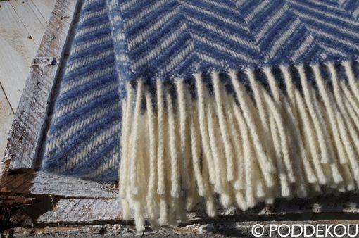Detail modrej deky so strapcami a vzorom rybia kosť.