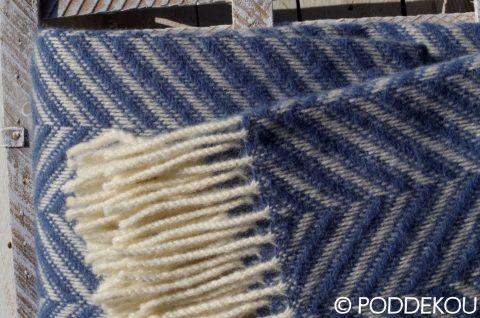 Detail vlnenej modrej deky so strapcami s herringbone vzorom