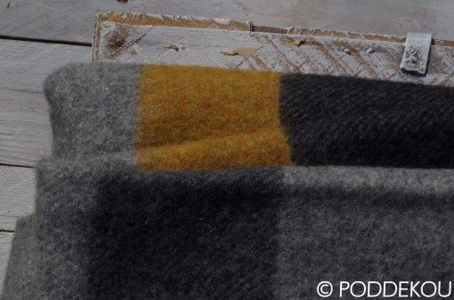 Moderná prúžkovaná deka v šedej, čiernej a žltej farbe.