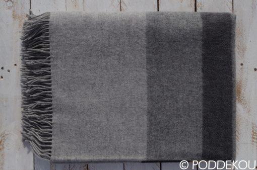 Moderný šedý prehoz so strapcami s prúžkami.