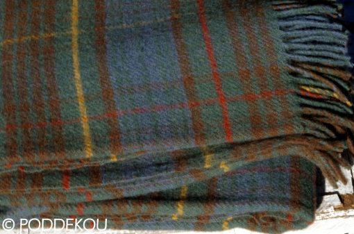 Vlnená deka s károvaným vzorom v zeleno-modrej farbe so strapcami.