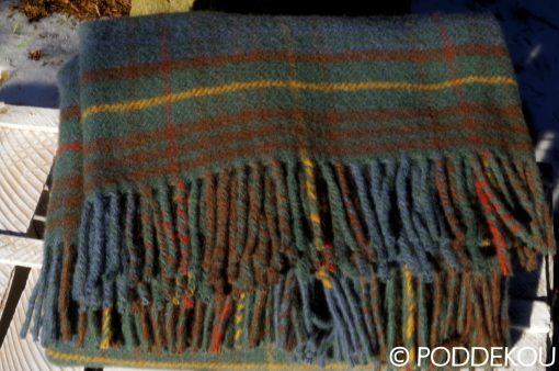 Tartanový prehoz z ovčej vlny v modrej, zelenej, hnedej farbe so strapcami.