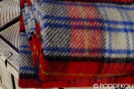 Detail deky v károvanom vzore v čeveno-bielo-modrej farbe so strapcami
