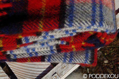 Prikrývka károvaná červeno-modrá zo 100% ovčej vlny so strapcami.