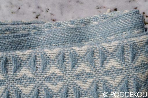 Pastelovo modrá deka so zaujímavým vzorom, detail deky z ovčej vlny, modrá deka, modrobiela deka
